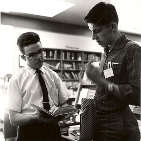 A part-time Moody Bookstore student employee showing a customer a book.